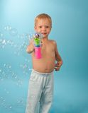 Little boy with pistol blowing soap bubbles Stock Photo