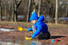 Little boy plaing with paper boats in spring Stock Images