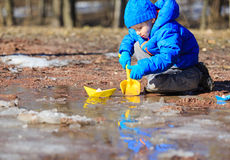 Little boy plaing with paper boats in spring Stock Image