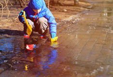 Little boy plaing with paper boats in water puddle Stock Photography