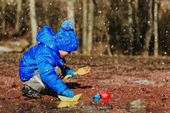 Little boy plaing with paper boats in winter Royalty Free Stock Images