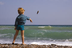 Little boy play on the beach. Little boy fling stones in sea Royalty Free Stock Photography