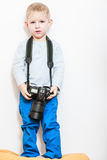 Little boy play with camera. Technology and childhood. Discovering and fun. Child play and take photo in home. Boy wear white shirt and blue trousers hold Royalty Free Stock Photo