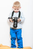 Little boy play with camera. Technology and childhood. Discovering and fun. Child play and take photo in home. Boy wear white shirt and blue trousers hold Royalty Free Stock Photography