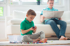Little boy play , father read newspaper Royalty Free Stock Photography