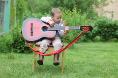 Little boy play in guitar outdoors Royalty Free Stock Photos