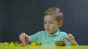 Little boy play with plasticine stock footage
