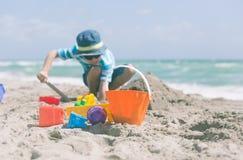 Little boy play with sand on beach Stock Photo