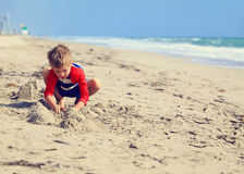 Little boy play with sand on summer beach. Cute little boy play with sand on summer beach Royalty Free Stock Photography