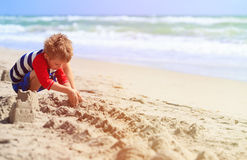 Little boy play with sand on summer beach Stock Images