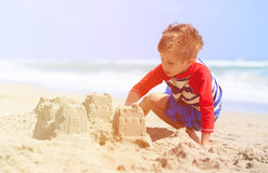 Little boy play with sand on summer beach Stock Image