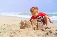Little boy play with sand on summer beach Stock Photo