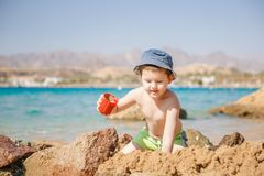 Little boy play with sand on summer beach. Red sea Royalty Free Stock Images