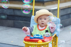 Little boy play soap bubbles. Portrait of little baby boy in stroller playing soap bubbles Royalty Free Stock Photo