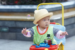 Little boy play soap bubbles. Portrait of little baby boy in stroller playing soap bubbles Stock Photo