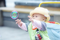 Little boy play soap bubbles. Portrait of little baby boy in stroller playing soap bubbles Stock Photography