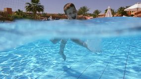 Little boy play in swimming pool, slow motion stock video footage