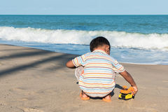 little boy play toy car on the beach Stock Images