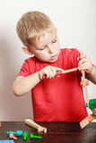 Little boy play with toy on table. Spending free time play and education for children. Little boy in red shirt play with colorful toy on table Stock Photo