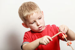 Little boy play with toy wooden screwdriver. Spending free time play and education for children. Little boy in red shirt play with toy wood screwdriver Stock Photos