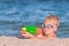 Little boy play with water gun. Little boy in a water glasses play with water gun on a sand beach of Black sea Royalty Free Stock Photo