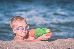Little boy play with water gun. Instagram stylization. Little boy in a water glasses play with water gun on a sand beach of Black sea. Instagram stylization Stock Images