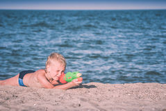 Little boy play with water gun 4. Instagram stylization. Little boy play with water gun on a sand beach of Black sea. Instagram stylization stock photo