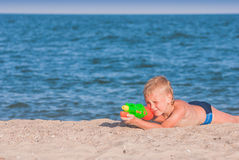 Little boy play with water gun 4. Little boy play with water gun on a sand beach of Black sea royalty free stock images