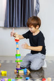 Little boy play wooden toys blocks on the floor, building towers. At home Stock Photo