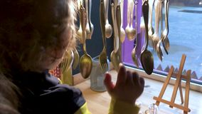 A little boy is played with decorative tableware in a cafe stock video