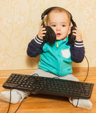 The little boy played with headphones and a keyboard Stock Image