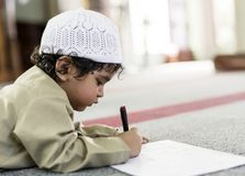 Little boy playfully drawing in a mosque during Ramadan stock photography