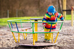 Little boy on playground in autumn Stock Images