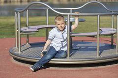 Little boy on a playground. Child playing outdoors in summer. Kids play on school yard. Happy kid in kindergarten or preschool. stock images