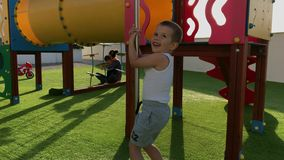 Little boy at playground. Little boy having fun at playground in a sunny day, handheld stabilised footage stock video