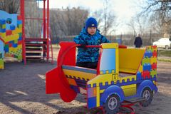 The little boy at a playground plays on the children's machine Royalty Free Stock Image
