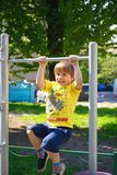 Little boy at playground plays sports. Fitness motivation Stock Images