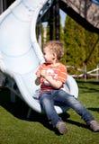 Little boy on the playground slide Stock Photos