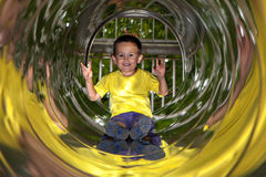 Little boy in playground tube Royalty Free Stock Image