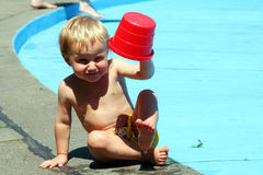 Little boy playing. A cute little caucasian white boy playing with a red bucket while sitting next to the swimming pool stock photo
