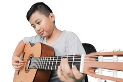 Little boy playing acoustic guitar. Portrait of a little boy sitting in the studio while playing an acoustic guitar, isolated on white background Royalty Free Stock Image