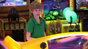 Little boy playing air hockey game