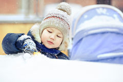 Little boy playing alone with toy in snow, close up. Outside, winter. Stock Photography