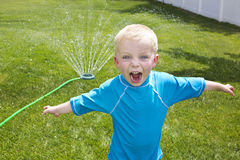Little Boy playing in the Backyard sprinklers Stock Image