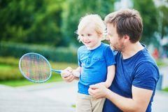Little boy playing badminton with dad on the playground Stock Photo