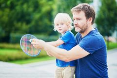 Little boy playing badminton with dad on the playground Stock Images