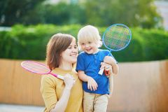 Little boy playing badminton with mom on the playground royalty free stock images