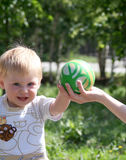 Little boy playing with ball. Little boy smiling and  reaching out to take the  ball Royalty Free Stock Photography