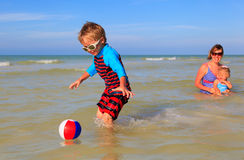 Little boy playing ball with family at the beach Stock Photography