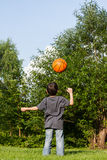 Little boy playing with ball. Little boy playing with his orange ball in the garden Royalty Free Stock Photos